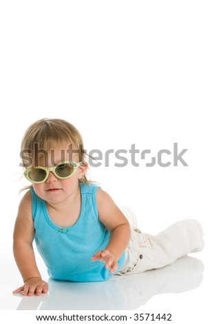 Young baby girl wearing sunglasses and a bright blue sleeveless top. Isolated on white with reflection. - stock photo