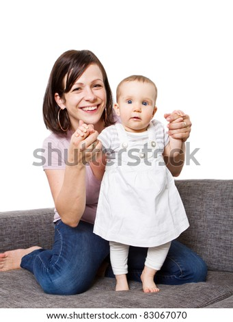 Young baby girl with cute dress and mother playing on the couch. - stock photo