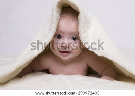 young baby lying on blanket and smiling - stock photo