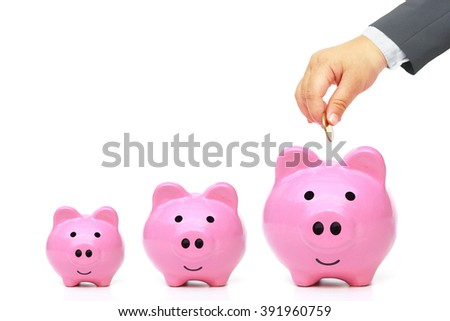 Young baby's hand in businessman suit giving golden coin to three piggy banks with different sizes - stock photo