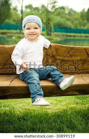 young baby sits on a wooden bench - stock photo