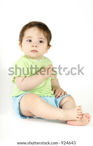 Young baby wearing casual top and shorts sheds a tear.