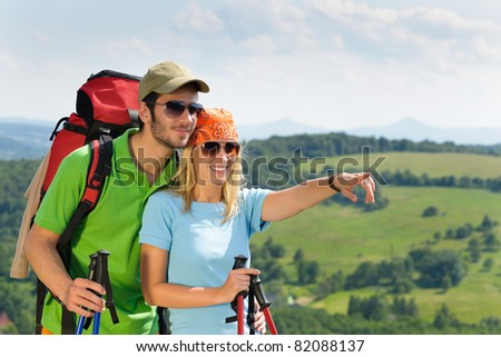 Young backpack couple with hiking poles beautiful panoramic view countryside - stock photo