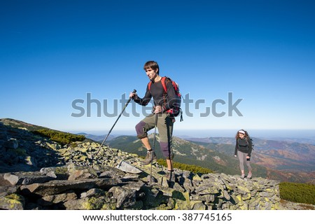 Young backpacker couple walking up rocky the mountain top, high altitude. Beautiful autumn mountain landscape on the background. Fall. - stock photo