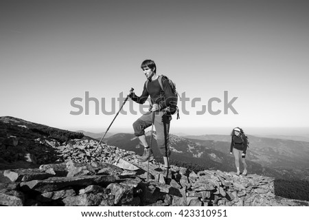 Young backpacker couple walking up rocky the mountain top, high altitude. Beautiful mountain landscape on the background. black and white - stock photo