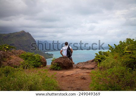 Young backpacker enjoying a valley view from top of a mountain. Hawaii, Oahu Makapu'u Point Lighthouse Trail. Summer vacation. - stock photo