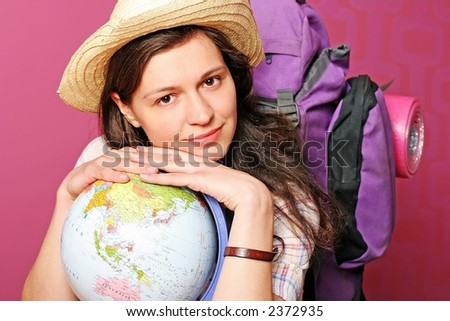 young backpacker setting for a journey around the world - on pink