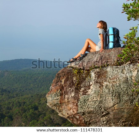 Young backpacker sitting on an edge of a mountain and enjoying valley view - stock photo
