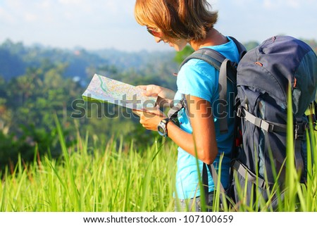 Young backpacker standing on a green meadow at sunny day and looking into a map - stock photo