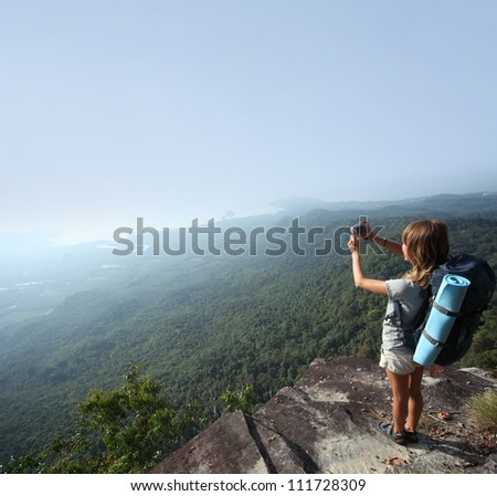 Young backpacker standing on top of a mountain and taking a picture of a morning valley