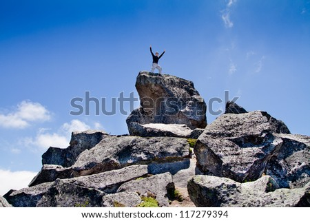 Young backpacker standing on top of a mountain, success concept