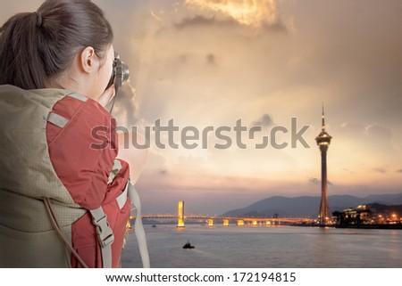 Young backpacker travel and take picture at Macau with famous travel tower. - stock photo