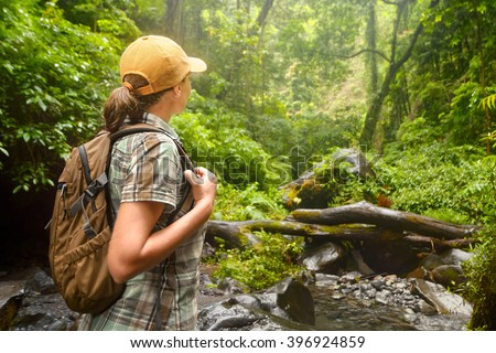 Young backpacker with backpack  traveling along rain forest. Lombok, Indonesia. Tourist hiking in the deep jungle - stock photo