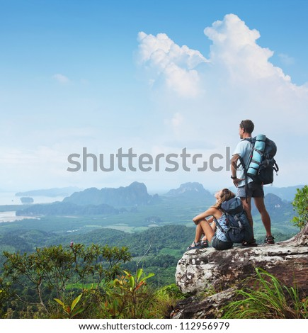 Young backpackers relaxing on top of a mountain and enjoying a valley view - stock photo