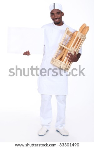 Young baker with a basket of baguettes and a board left blank for your message - stock photo