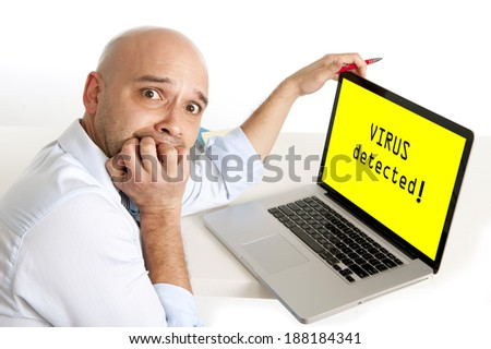 young bald latin worried and scared business man sitting at office desk biting fingernails watching his computer infected with virus and damaging his work files - stock photo