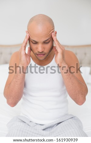 Young bald man suffering from headache in bed at home