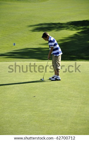 Young ball ready to putt a golf ball on a golf course.  The photo was taken in the late afternoon when the sun was getting low in the sky. - stock photo