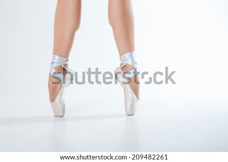Young ballerina dancing, closeup on legs and shoes, standing in pointe position. - stock photo