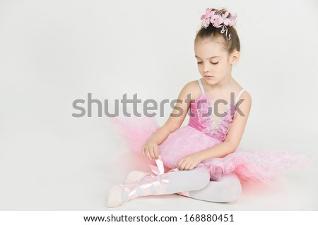 young ballerina girl in a pink dress on a light background - stock photo