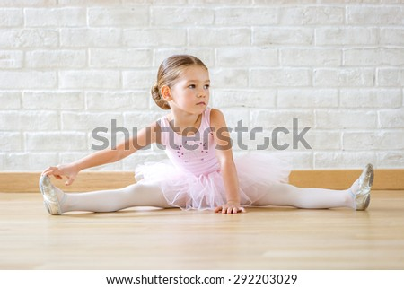 Young ballerina in pink clothes sitting on the floor during the training in dance class. - stock photo