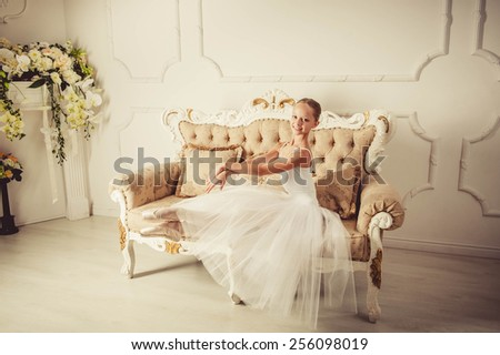 young ballerina is dancing in white hall. She in classic dress is clothed. - stock photo