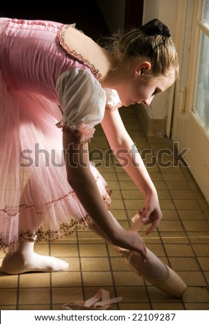 young ballerina puts on pointe  before appearance - stock photo