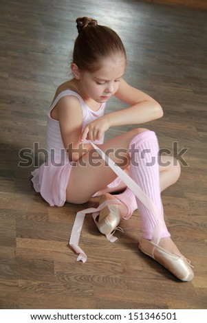 Young ballerina puts on pointe in ballet class at the old wooden dance floor - stock photo