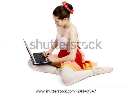 Young ballerina sits on floor with computer