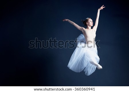 Young ballerina with a perfect body is dancing in the photo studio. The dancer wears a fashionable dress. The photo is taken in minimal style, showing the beauty of a such classical art like ballet.  - stock photo