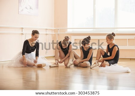 Young ballerinas putting on pointe shoes while sitting on floor in ballet class - stock photo