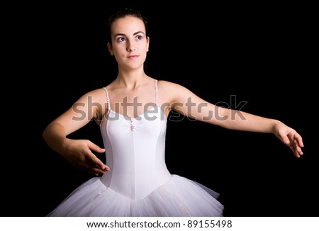 Young ballet dancer posing against black background - stock photo