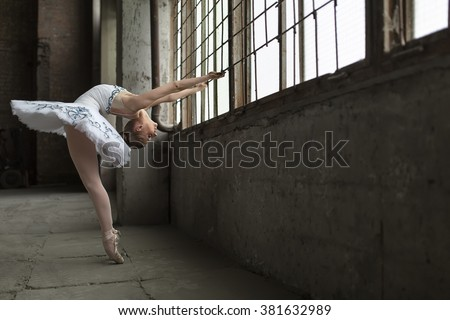Young ballet dancer posing next to windows in an old industrial building. She is standing on pointes while she holds the grille during tilting back. Indoor. Horizontal. - stock photo