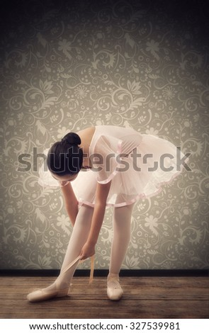 Young ballet dancer while tying ballet shoes - stock photo
