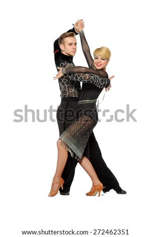 Young ballroom dancers in formal costumes posing against a solid background in a studio - stock photo