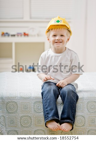 Young barefoot boy sitting on bed in bedroom wearing hard-hat