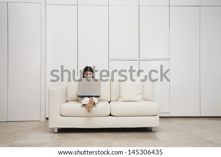 Young barefoot girl using laptop on sofa - stock photo