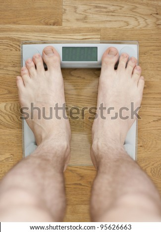 Young barelegged male standing on a transparent digital glass scale on a wooden floor. Room for your text in the display.