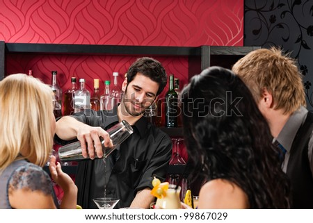Young barman prepare drink friends at cocktail bar - stock photo