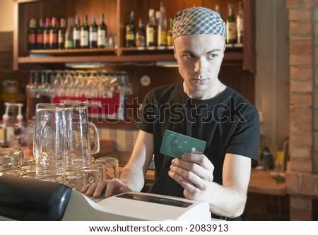 young  barman verifying credit card or cheating