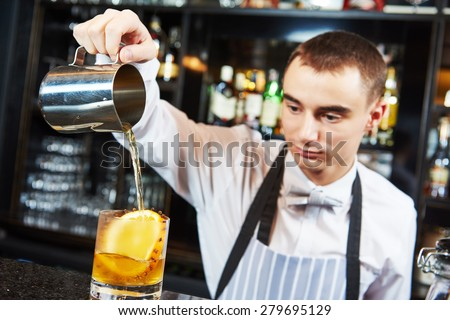 young barman worker at bartender desk in restaurant bar preparing coctail - stock photo