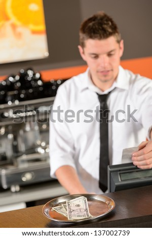 Young bartender in uniform taking cash USD in bar - stock photo