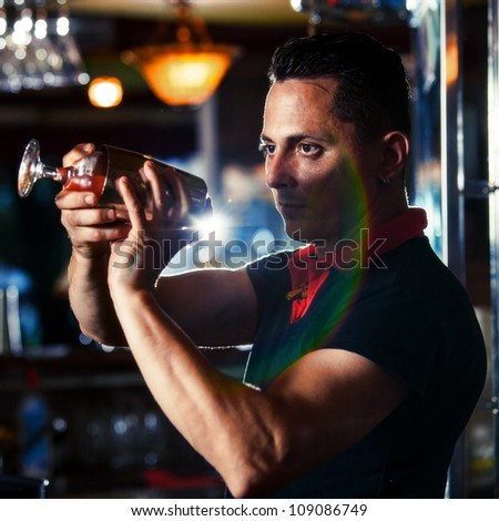 Young bartender with cocktail - stock photo