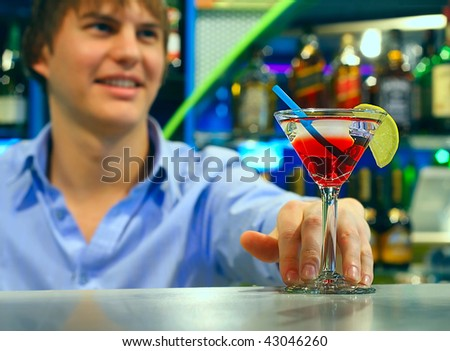 Young bartender with cocttail on table