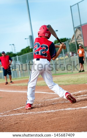 Young baseball kid swinging the bat during a game. - stock photo