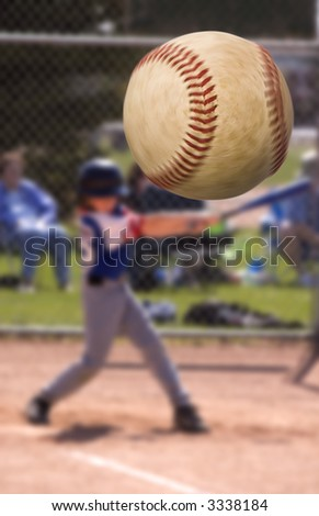Young baseball player hitting a home run , focus on the ball with motion blur - stock photo