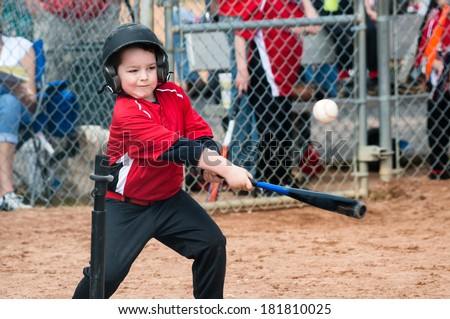Young baseball player hitting ball off a tee during game - stock photo