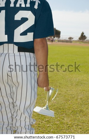 Young baseball player holding trophy - stock photo