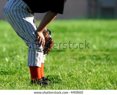 Young baseball player in outfield; space for copy. - stock photo