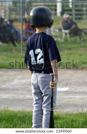 Young baseball player next up to bat.